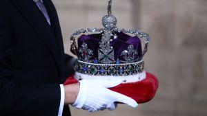 Händer som håller i Drottningens Imperiestatskrona på en röd dyna.