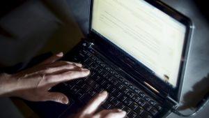 Händer knapprar på tangentbordet till en bärbar dator.