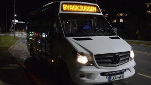 """Det är mörkt. Bussen är vit och framtill lyser texten """"Byaskjussen""""."""