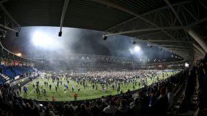 Fotbollsplanen vid Tölöstadion full med människor efter Finlands fotbollsmatch mot Liechtenstein.