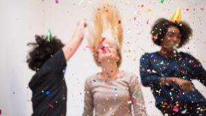 Tre människor i partyhattar dansar i konfettiregn