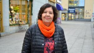 En kvinna står på en gågata inne i en stad.
