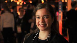 En ung dam i svarta kläder ler mot kameran.