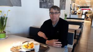 En man sitter vid ett bord och äter lunch.
