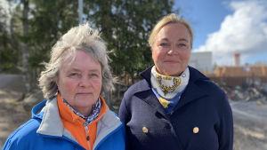 Två kvinnor står utomhus och ser in i kameran.