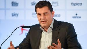 En man i mörk kavaj o vit tröja har sina händer vridna lite snett uppåt från ett podium med mikrofon med munnen lite öppen och med intensiv blick framåt.