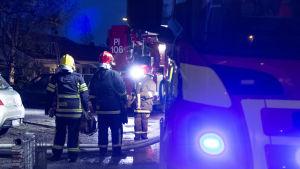 En brandbil syns i förgrunden till höger. Till vänster står tre brandmän med ryggen mot kameran. I bakgrunden syns ytterligare en brandbil och ett hus längre bort.