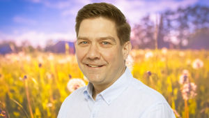 Thomas Blomqvist ler rakt in i kameran med en sommaräng som syns i bakgrunden.