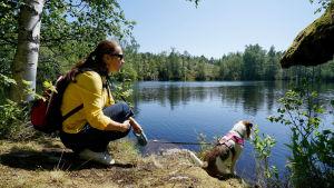 En kvinna sitter på huk med sin hund vid en sjö i skogen.