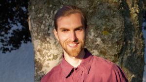 Nils Titus Östbrant fotograferad framför ett träd. Han har rödaktigt skägg och tittar rakt in i kameran.