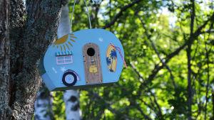 En ljusblå fågelholk i ett träd.