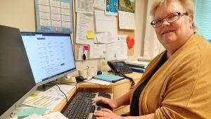En kvinna sitter vid sitt skrivbord och tittar in i kameran.