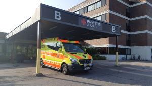 En ambulans är parkerad utanför jouren vid Lojo sjukhus.