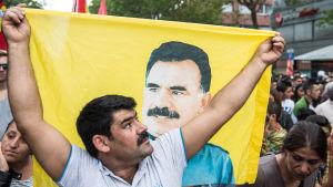 En man i ett demonstrationståg håller upp en gul fana med ett porträtt på PKK-grundaren Abdullah Öcalan.