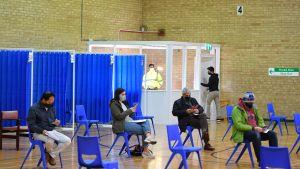 Människor sätter sig en stund efter att ha fått covid-19-vaccin i Storbritannien 8.12.2020