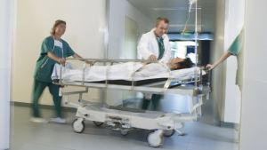 Patient i dropp ligger på bår, rullas fram av läkare