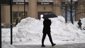 En person helt klädd i svart gömmer sig under ett svart paraply. I bakgrunden en enorm snöhög.