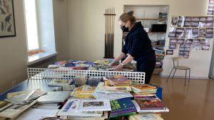 Linda står och sorterar böcker som ska tas med i flytten.
