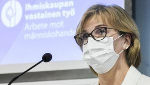 Anna-Maja Henriksson bär munskydd och glasögon. Bakom henne syns en presentation av en handlingsplan.