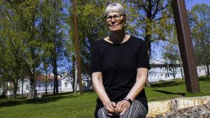 En medelålders kvinna sitter på en stor stubbe på en gräsplan och ler lite. Solen skiner. I Bakgrunden syns gräsmatta, gamla trähus och delar av en klocka samt pelarna som håller upp vajern där klockan hänger.