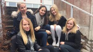 fem flickor sitter på trappa