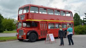 En gammal röd buss står parkerad och två personer tittar på den.