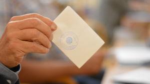 En hand håller i en stämplad vit lapp, en valsedel i fullmäktige.