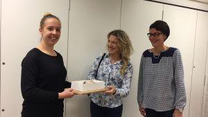 Lilly Thomander lämnar in sitt bidrag till Hanna Mehtonen-Rinne och Cathina Wretdal-Lindström på bildningskansliet.