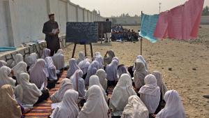 Grupper med elever undervisas på en gårdsplan i Afghanistan