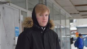 Skolelev Mattias Kewin väntar på bussen.