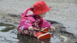 Barn leker i vattenpöl