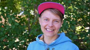 En bild på en kvinna med rosa keps och blå tröja som står framför en buske. Personen på bilden är Virve Savoila