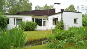 egnahemshus med trädgård och damm