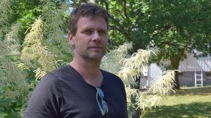 En man står i en trädgård.