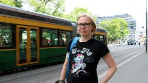 Fredrika Biström står på trottoaren. Bakom henne kör en spårvagn.