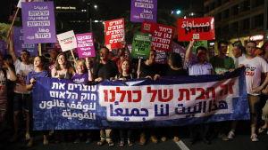 """Israeler i Tel Aviv protesterar mot den nya nationalstatslagen. På en stor banderoll står det """"Det här huset tillhör oss alla"""" på Hebreiska."""