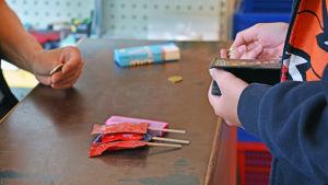 Händer, pengar och varor vid butikskassa