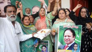 Nawaz Sharifs politiska supportrar firar Sharifs frigivning från fängelse. De sträcker upp armarna, håller i plakat med bilder på Sharif.