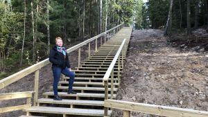 En kvinna står halvvägs uppför trappa.