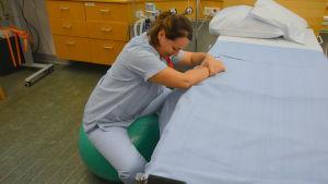 Barnmorskan Petronella Sevelius visar hur man kan lindra smärtan under en förlossning.