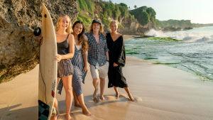 Neljä nuorehkoa ihmistä seisoo rannalla, yhdellä surffilauta kädessä. Katsovat kameraan ja hymyilevät.