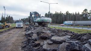 En grävmaskin lastar uppbruten asfalt på en lastbil.