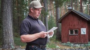 Bredaxlad man i beige skärmmössa, svart t-shirt och svarta jeans håller i ett papper och läser från det.