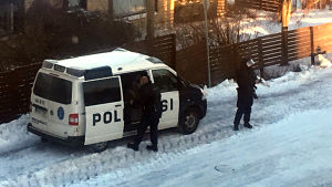 Två beväpnade poliser vid polisbil