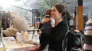 Elisabeth Glatz sitter vid enn cafébord med sin baby i famnen
