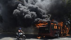 En oppositionsanhängare passerar en brinnande buss under gårdagens kravaller i Caracas