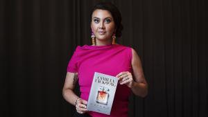 Camilla Läckberg poserar med sin bok En bur av guld