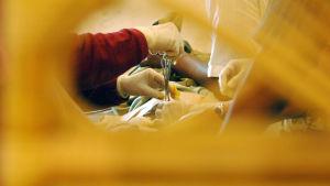 En sax och plasthandskar när en pojke blir omskärd i Indonesien