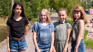 Fyra flickor står på led på en grusväg.