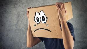 en man håller en stor pafflåda på sitt huvud - pafflådan har en ledsam min